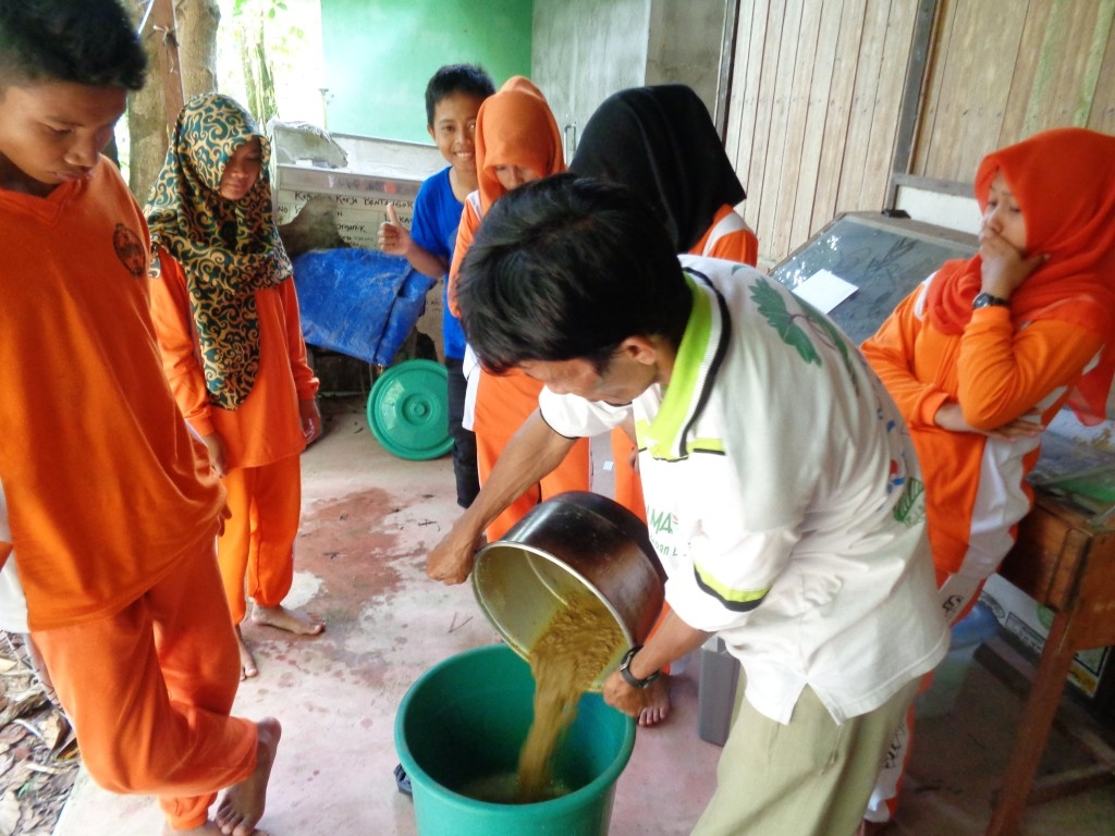 Sustainable Livelihoods team member Asbandi teaches a school group how to make organic fertilizer