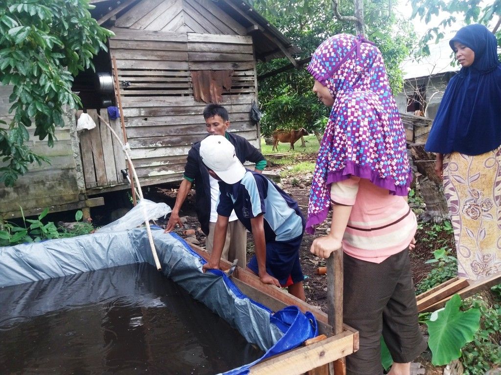 Trainee fish farmers in Tanjung Gunung village check on their pond. This simple set up can be built in just a few hours from wood, nails, and a tarp. Just add baby fish!